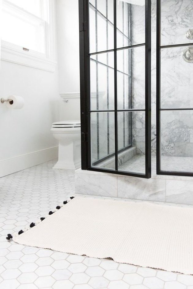 bathroom rug idea in white and black bathroom with hexagonal floor tile