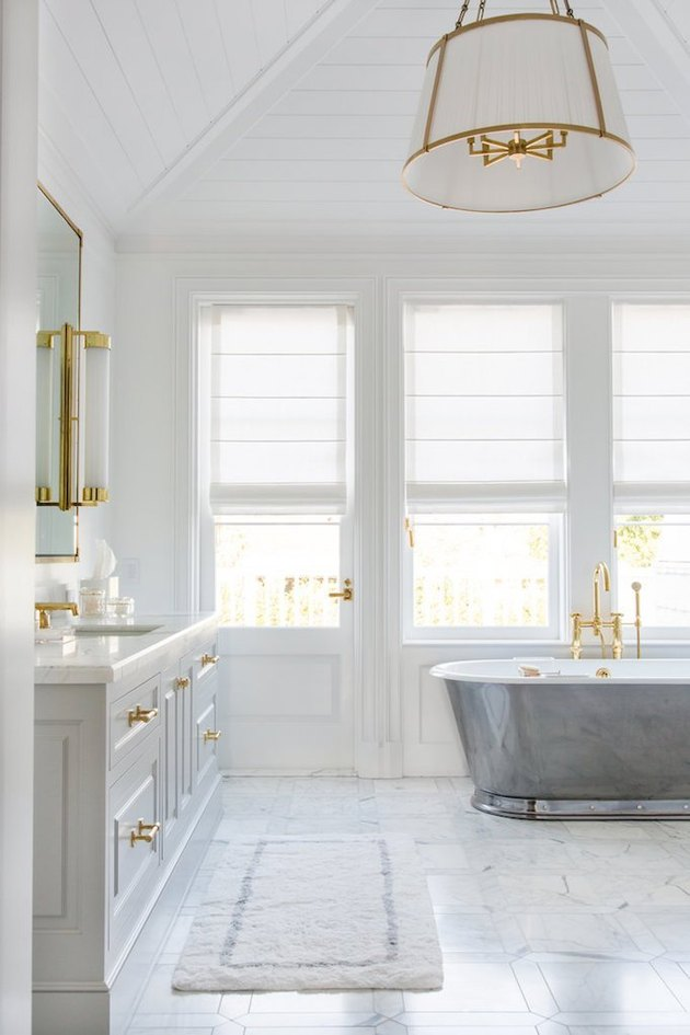 bathroom rug idea in all white bathroom with gold hardware