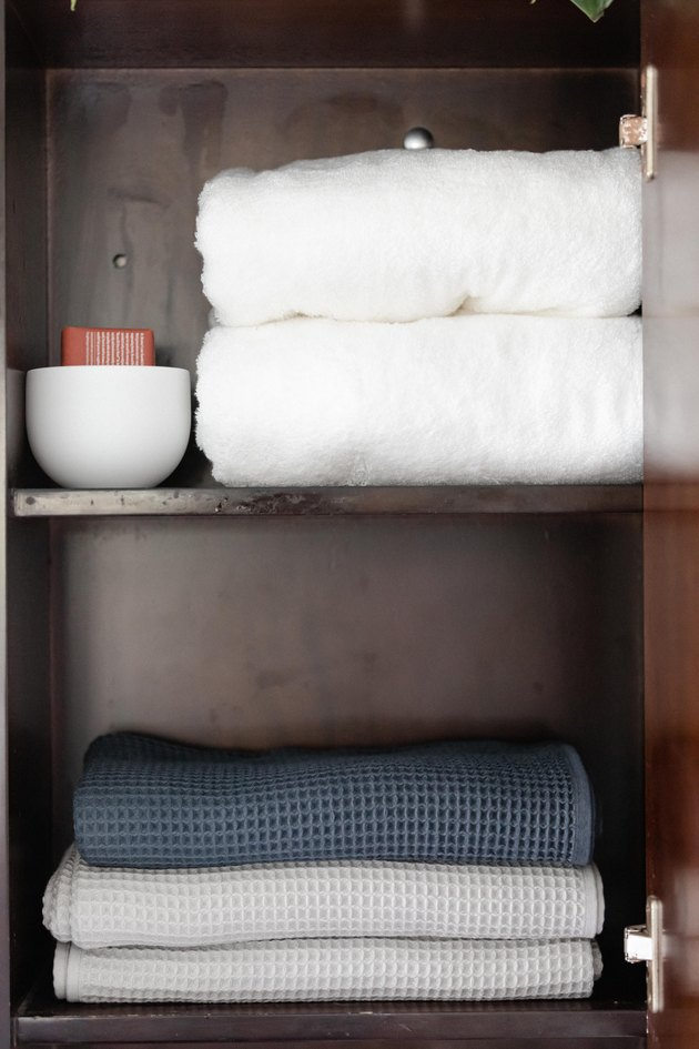 bathroom cabinet with folded towels