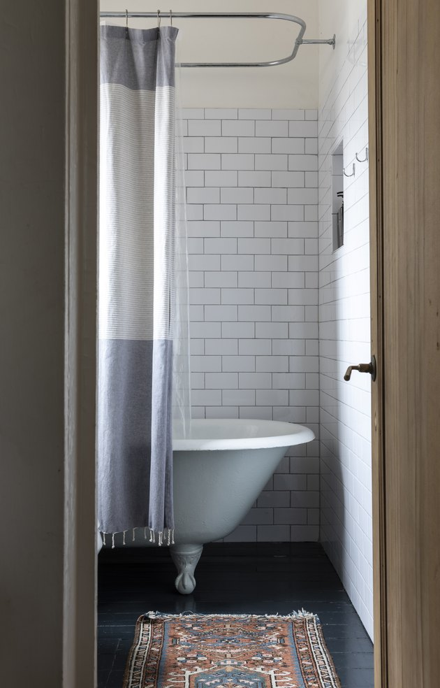 claw-foot bathtub/shower, shower curtain, subway tile walls and rug