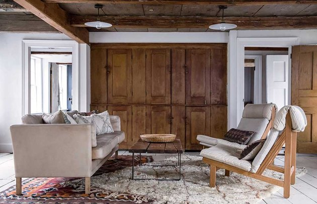 rustic small living room idea with wood ceiling and layered rugs