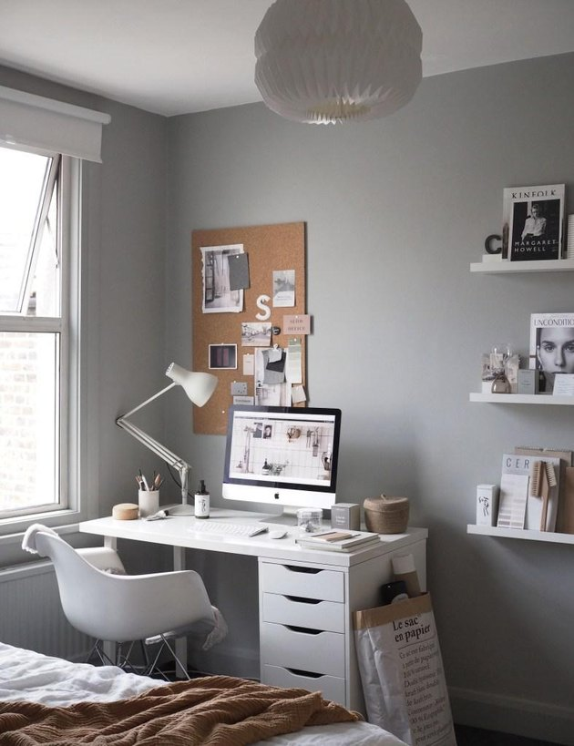 Gray walls with a small white desk in the corner next to a window