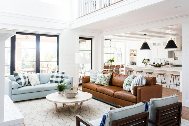 Traditional white living room with brown leather sofa and round coffee table