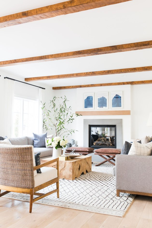 Living room with exposed wood beams and accent benches and wood block coffee table