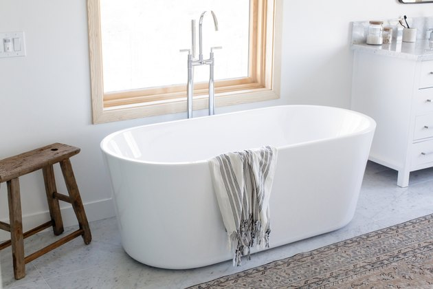 stand alone tub in front of a window