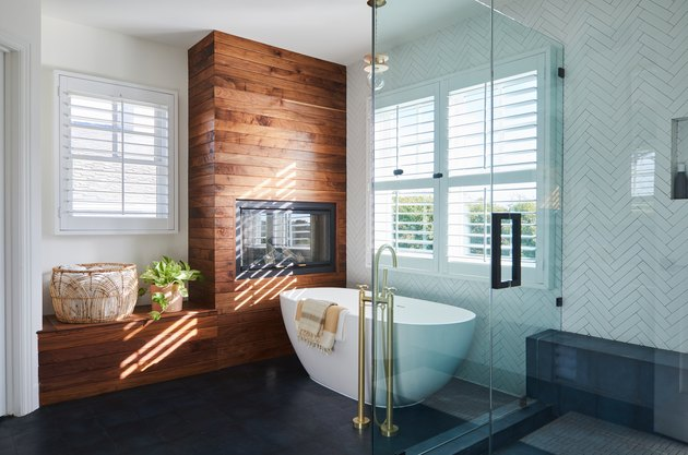 Modern bathroom trend with wood clad fireplace and herringbone tile walls