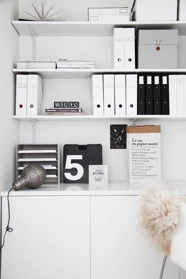 Black-and-white folders on a white desk with graphic accents