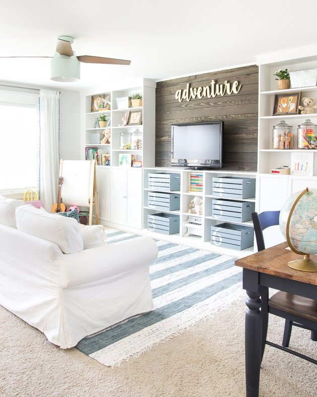 family room storage with white built in shelving with flat screen tv, storage bins, white couch, blue striped rug.