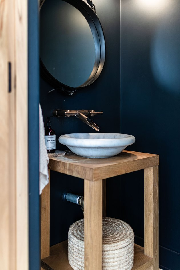 deep blue walls, round mirror with black trim, vessel sink with gold faucet, wood vanity countertop