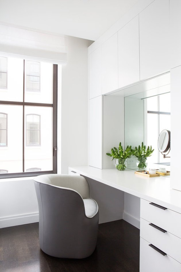 all-white bathroom makeup vanity with frameless mirror