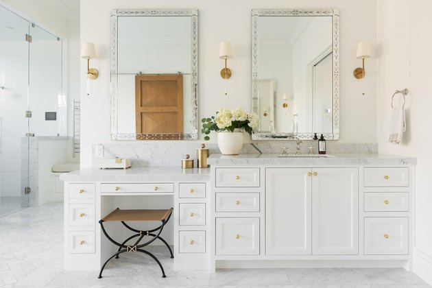 bathroom makeup vanity with white cabinets and marble countertop