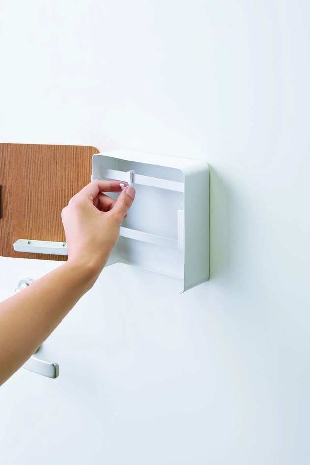 person placing hook into square magnetic key cabinet on door