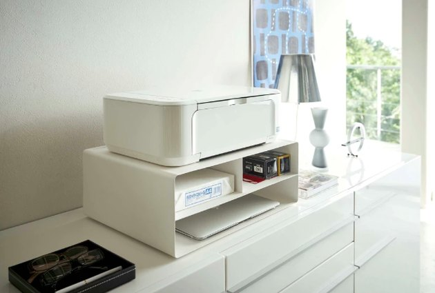 console with printer on white stand