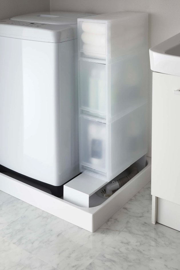 white laundry appliance with storage caddy nearby