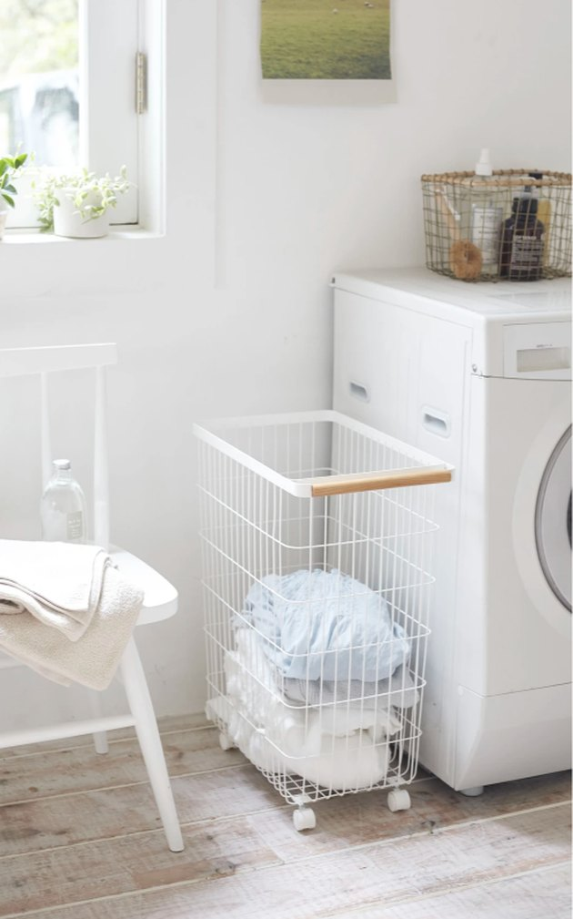 white laundry machine with rolling laundry basket nearby