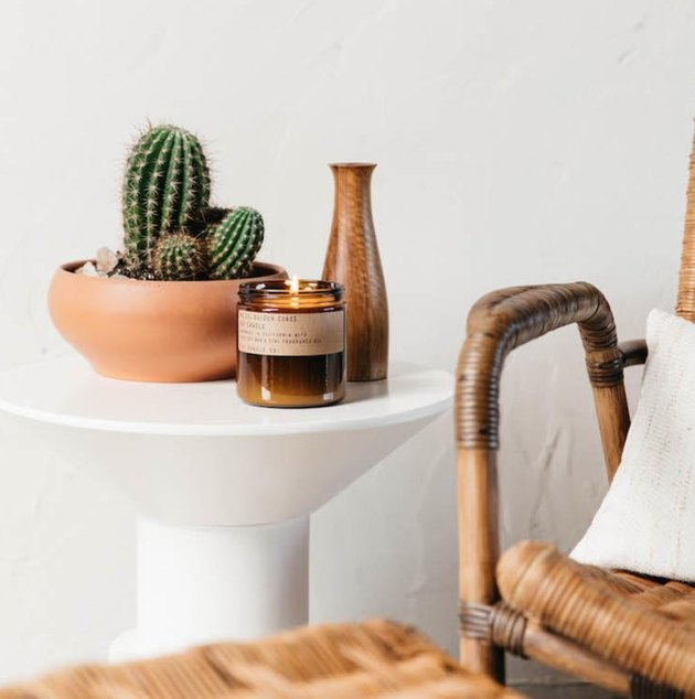 Cactus in terra cotta pot, P. F. Candle Company candle, ceramic vase, white end table, cane side chair, white pillow.