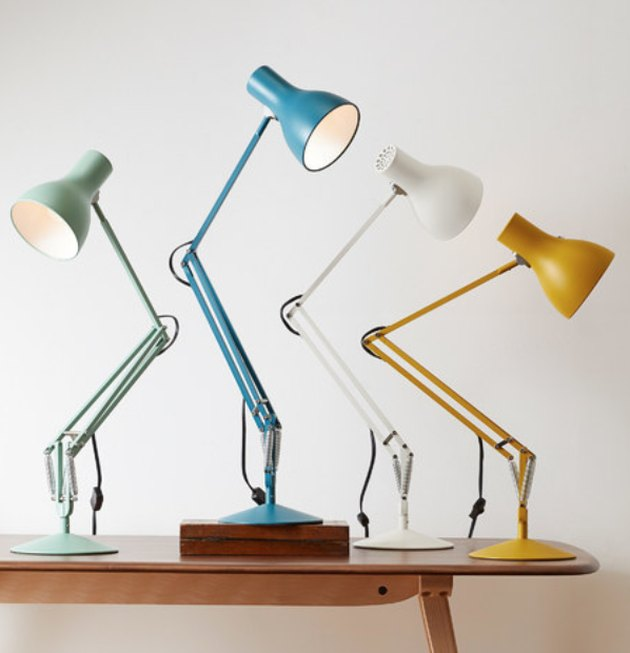 Four desk lamps in green, blue, white and yellow on top of wood table.