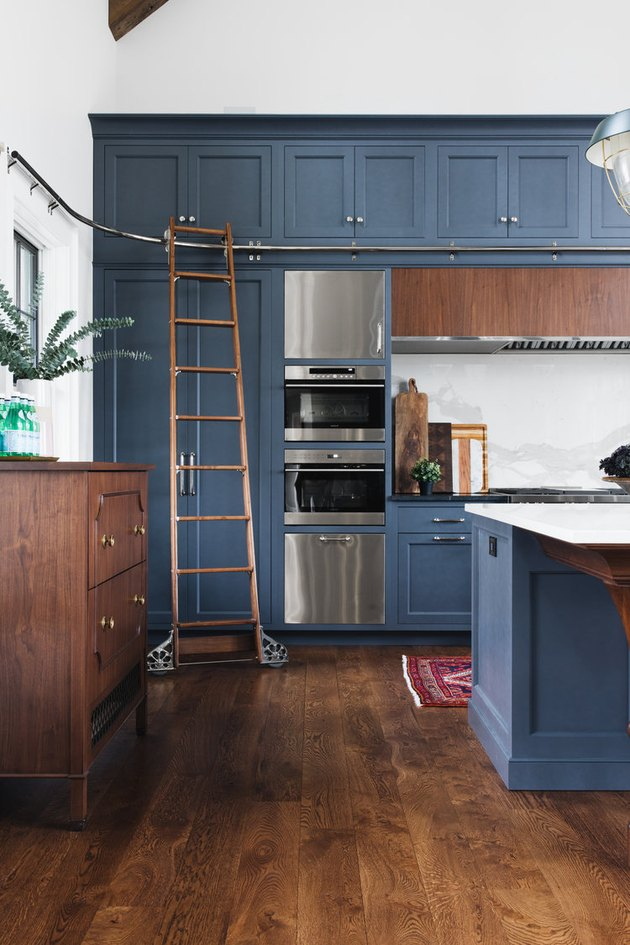 blue tall kitchen cabinets with library ladder