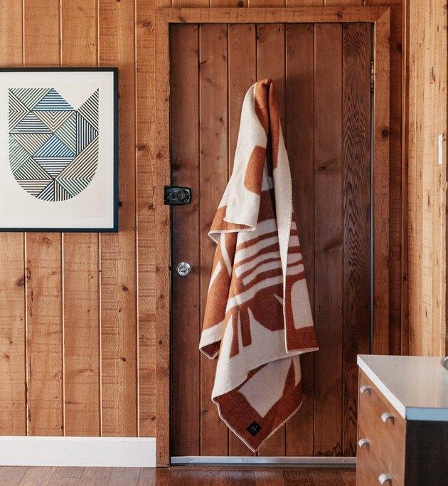 Throw blanket hangs on back of door in wood paneled room, with wood dresser and art print on wall.