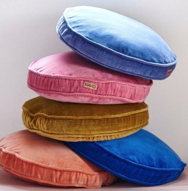 Round velvet throw pillows in light blue, pink, gold, royal blue and orange.