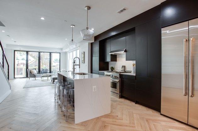 modern black tall kitchen cabinets and herringbone floors