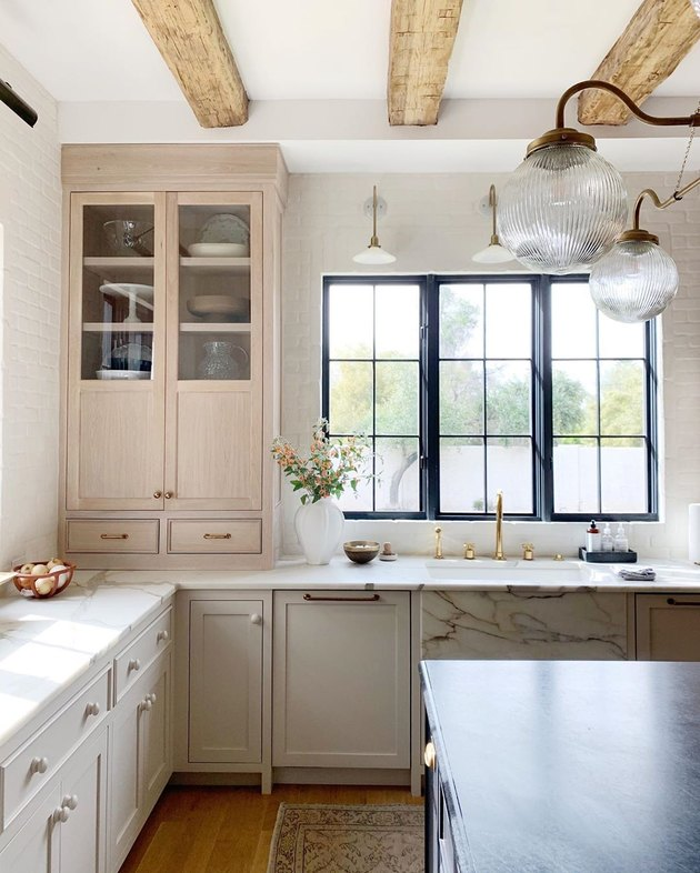 neutral tall kitchen cabinets with rustic wood ceiling beams