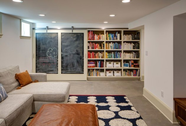 Recessed basement lighting in off white basement with beige sectional, leather ottoman, white and blue graphic area rug, built in bookcases and blackboard.