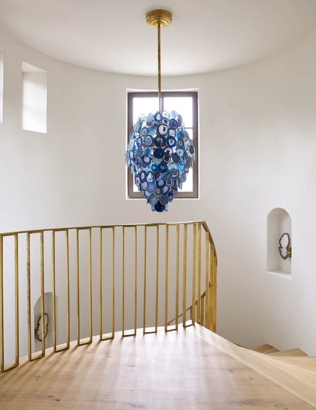blue chandelier over gold modern stair railing