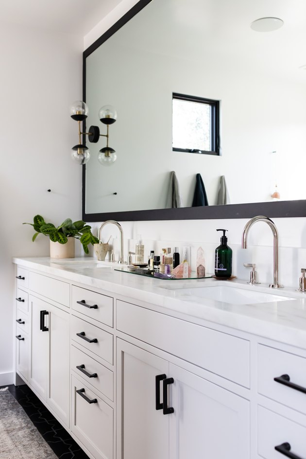 Bathroom with large mirror and sconce on mirror.