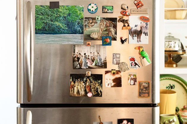 close up of stainless steel fridge with pictures tacked to it