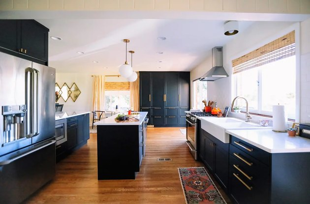 navy tall kitchen cabinets with brass hardware and white countertops