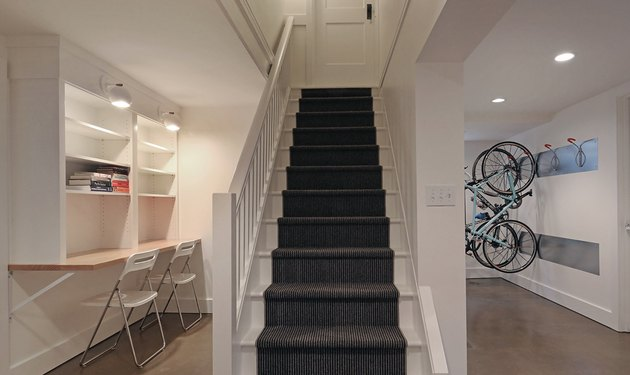 basement lighting in white basement with staircase, work area with built in shelves, two chairs, white sconces, and recessed lighting