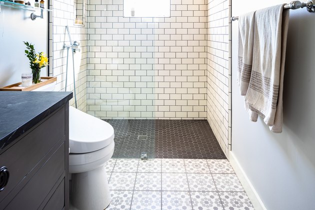 open shower with glass door, black hexagon floor tile with drain in the center, white subway wall tile, purple patterned floor tile, white toilet, two towels hung up