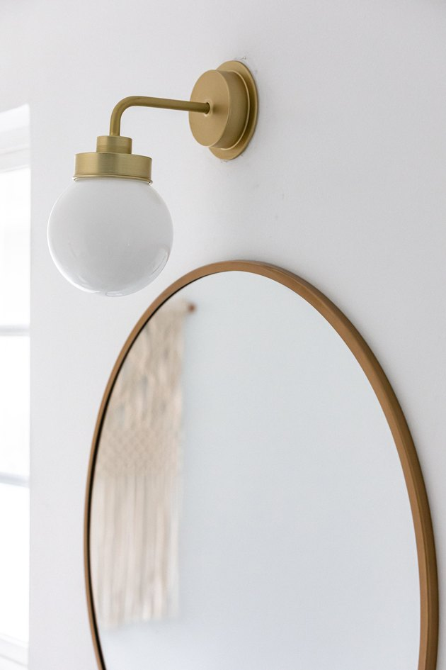 close up of bathroom light and circular mirror