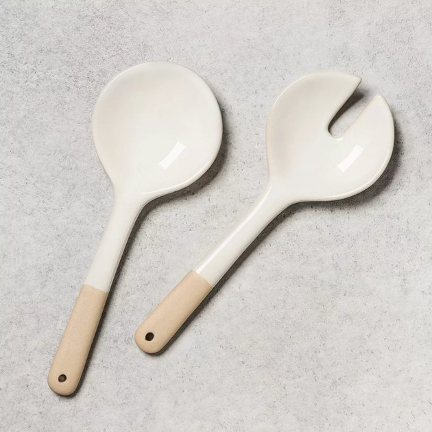 two salad tongs with white top and wood handle