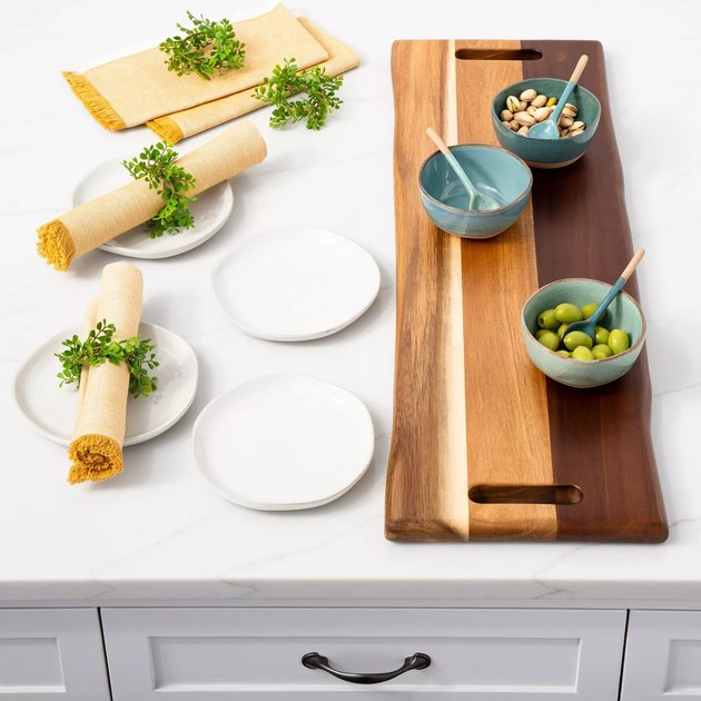 overview photo of plates, napkins with faux leaf rings, and a wood serving board with three bowls