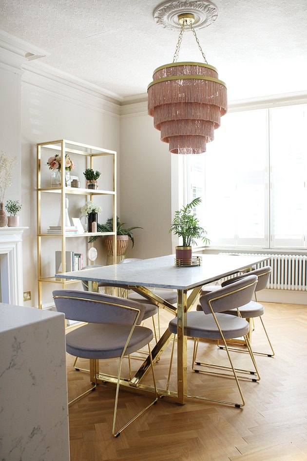 Pink and white art deco dining room with pink fringe chandelier and blue velvet chairs