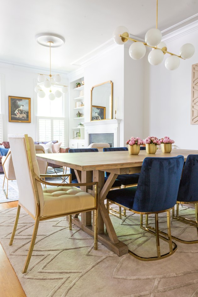 White and brass art deco dining room with velvet chairs and modern chandelier
