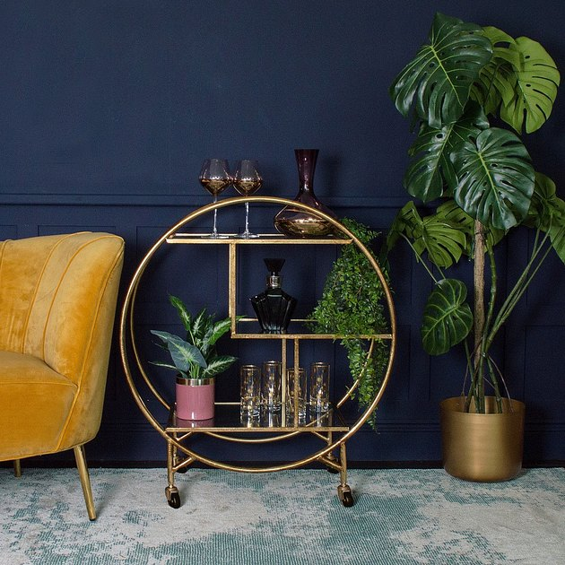 art deco apartment with blue room with brass bar cart