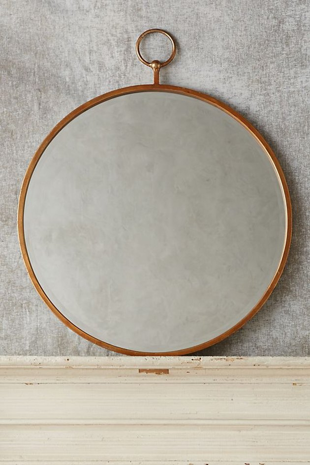 Circular wall mirror with brass border and small hanging loop