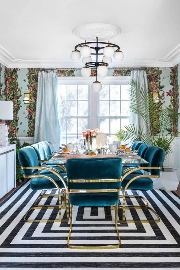 Black and turquoise art deco dining room with velvet and brass chairs and globe-style light fixture