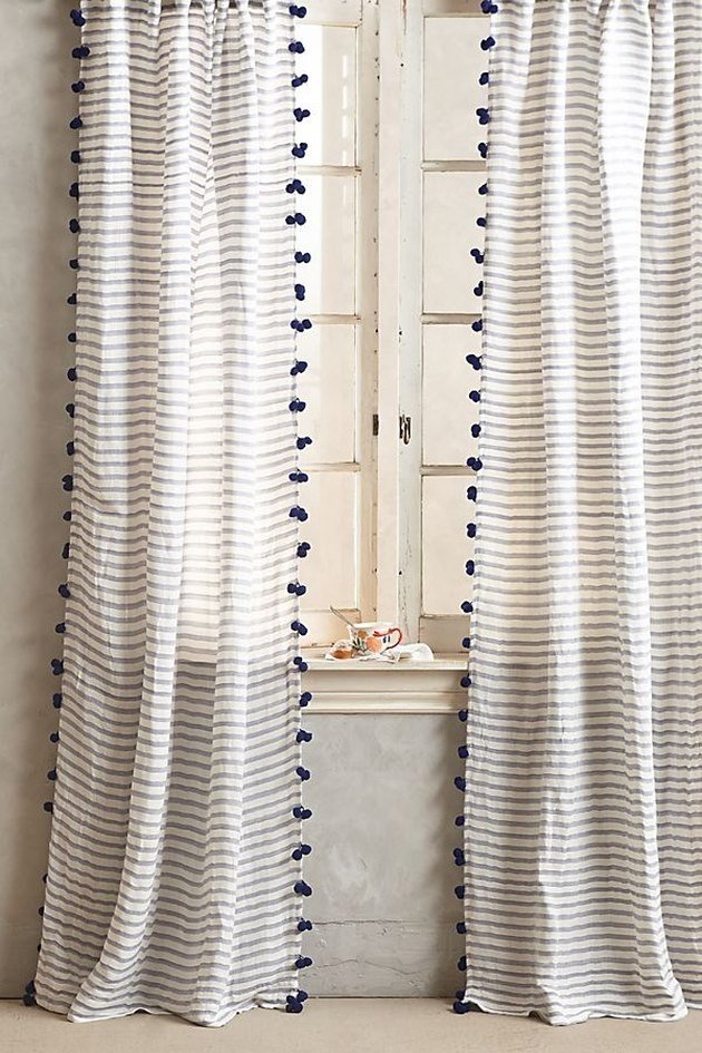 Sheer curtains with light gray horizontal stripes and small gray tassels