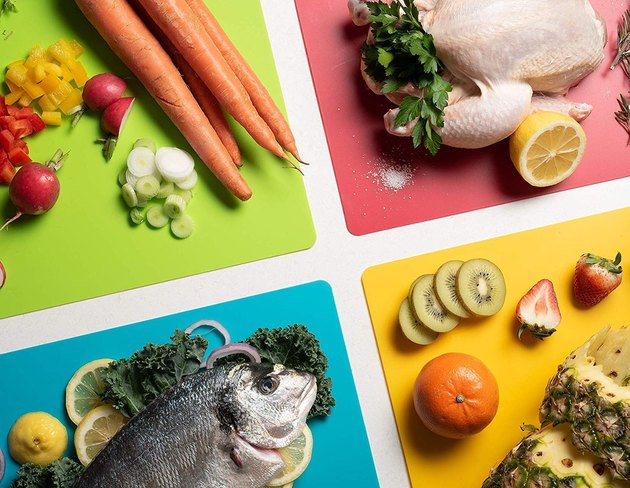 four different colored cutting boards with different foods