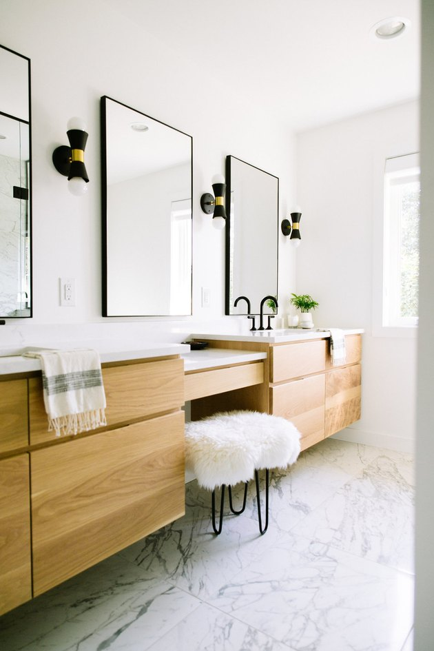 minimalist bathroom vanity with three large mirrors and a white stool.