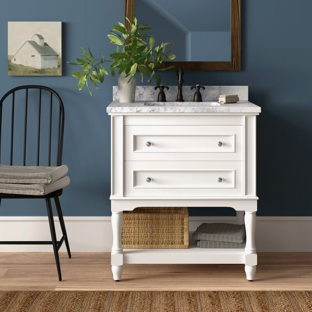 White country bathroom vanity with blue wall and barn painting
