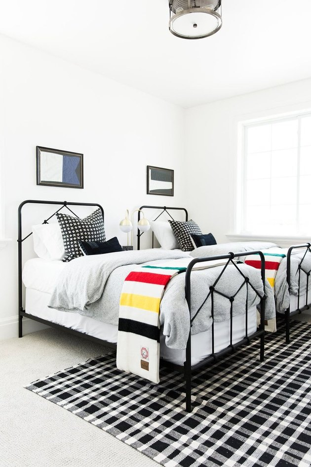 Kids' minimalist bedroom with black and white decor and flag wall art