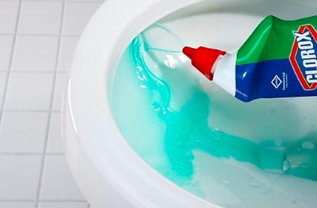 bottle of toilet bowl cleaner over toilet