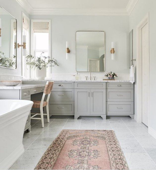 bathroom makeup vanity with gray cabinets and marble countertop