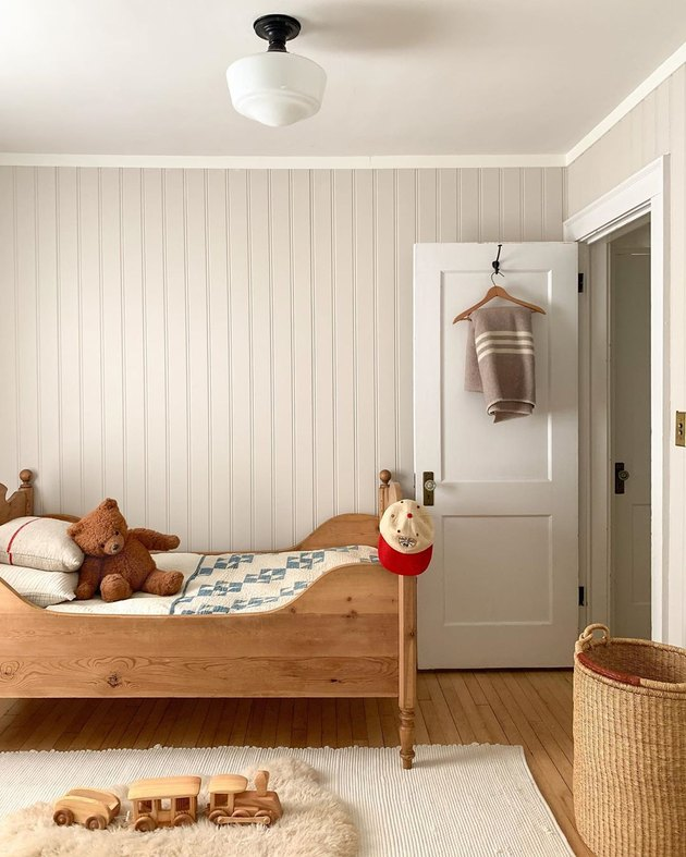 Kids' minimalist bedroom with wood bed and vintage decor