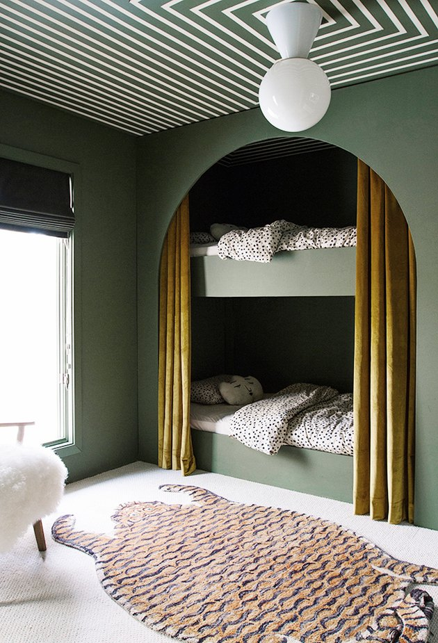Kids' minimalist bedroom with green walls, tiger area rug, and modern ceiling light